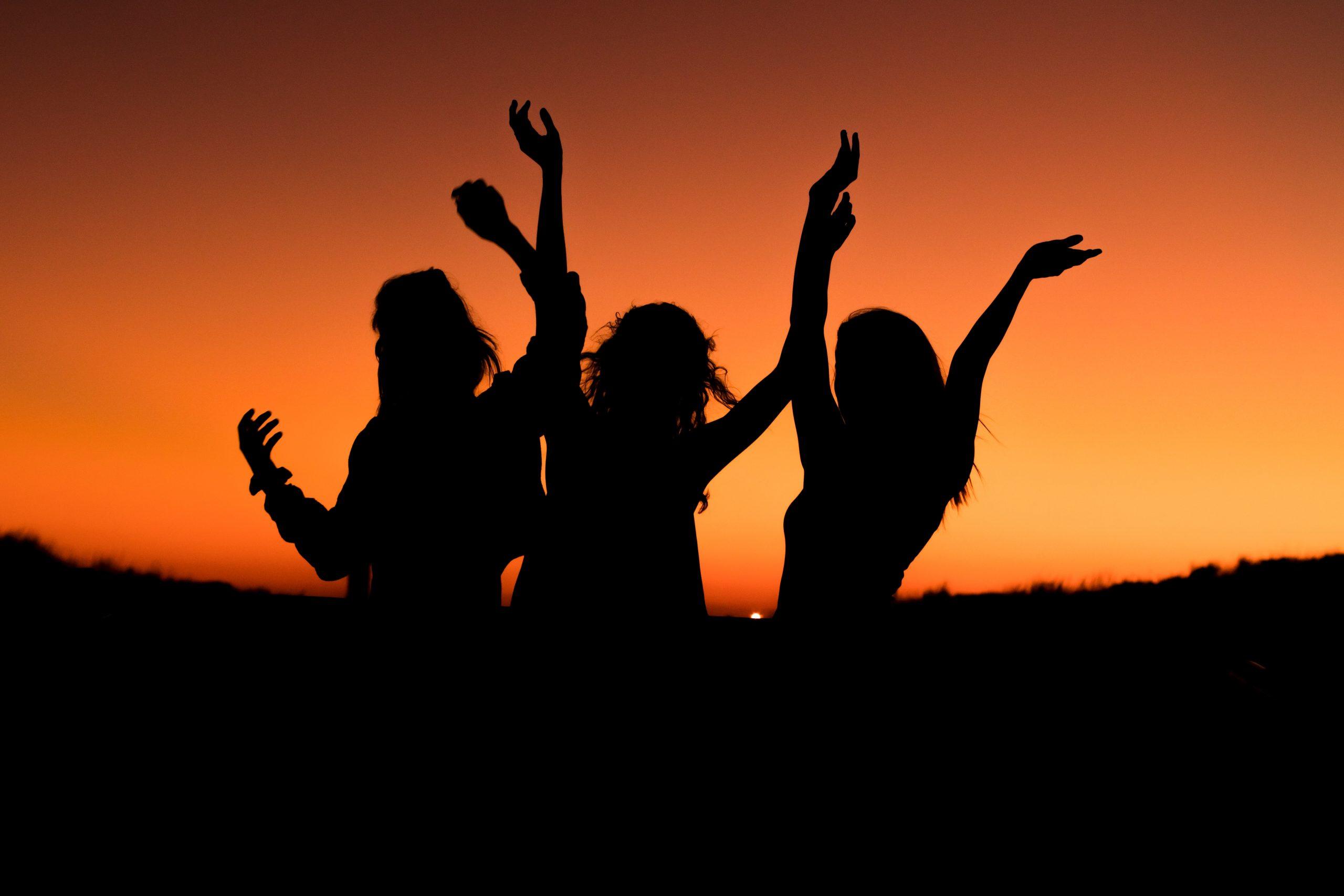 women dancing in the sunset